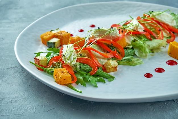 白いプレートにルッコラ、トマト、オレンジ、レタスの葉のアジアンスタイルのベジタリアンサラダ