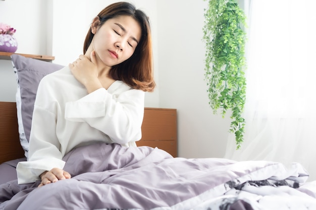 Asian suffering from neck pain waking up in bed
