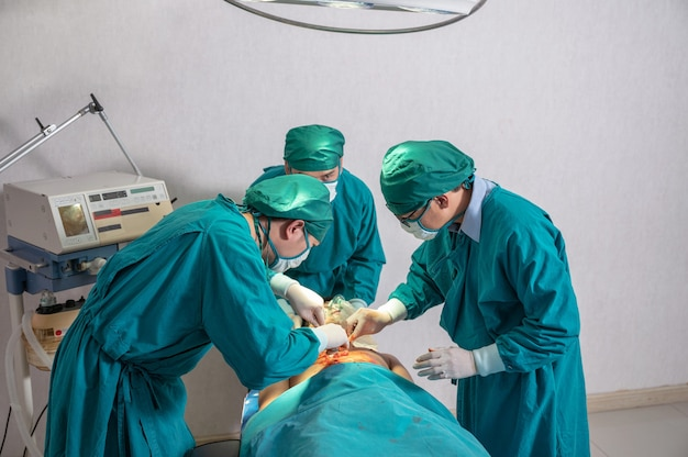 수술 가운을 입은 아시아 외과 팀이 병원 수술실에서 중상을 입은 환자를 수술합니다.