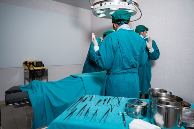 Asian surgeons team in surgical gown performing surgery a seriously injured patient and surgical equipment in operating room at hospital