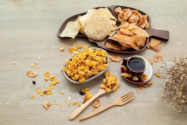 아시아의 달콤하고 짠 스낵, 맛있는 혼합 콘플레이크, 튀긴 바나나, 튀긴 타로, 견과류, 포도, 캐러멜이 나무 배경의 자연광에 있습니다. 차 한 잔과 복사 공간이 있는 달콤한 간식