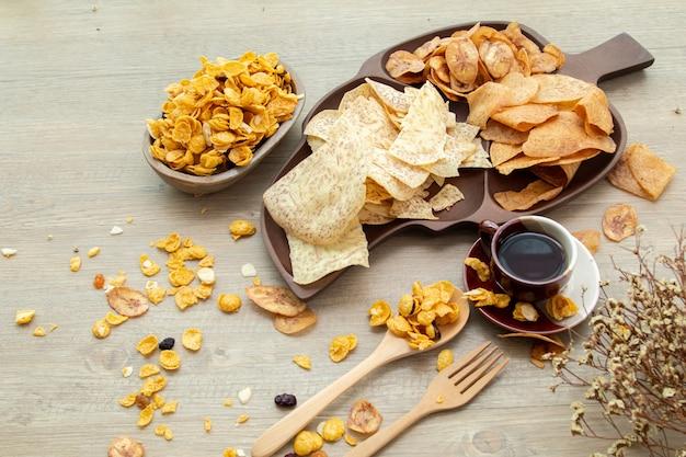 アジアの甘くて塩辛いスナック、おいしいミックスコーンフレーク、揚げバナナと揚げタロ、ナッツ、ブドウ、キャラメルを木製の背景の自然光で。お茶とコピースペースの甘いおやつ