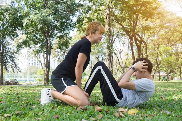 Asian sweet couple exercising together with smile on their faces on soft grass encircle