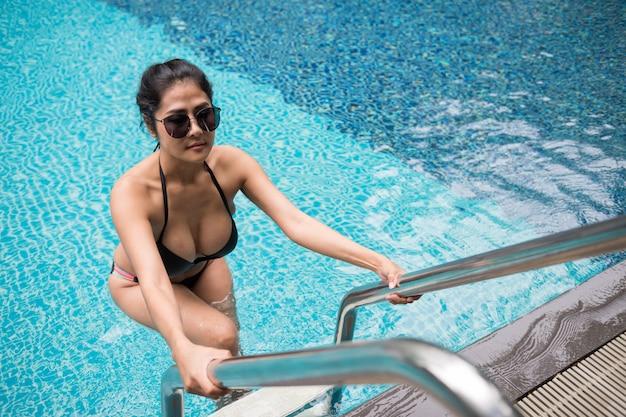 Asian tan sexy woman at swimming pool