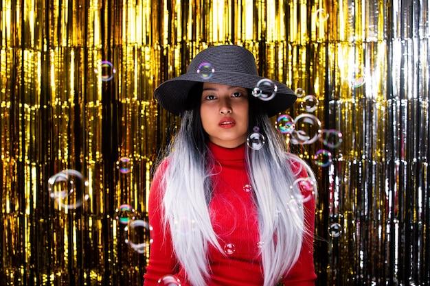 アジアの日焼け肌の女の子は暗い帽子をかぶる白い髪の赤いドレスは空気中で泡を吹く、笑顔と楽しい、スタジオ照明ゴールドの背景コピースペースで金色のホイルカーテンパーティーで幸せを感じる