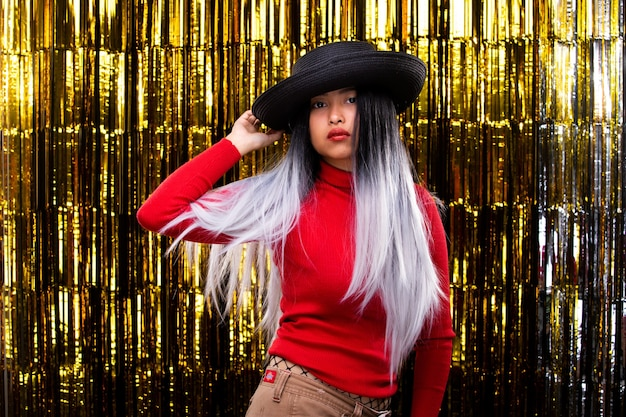 アジアの日焼け肌の女の子は、空気中に白い髪を投げて暗い帽子をかぶって、スピン笑顔を回し、楽しいスタジオ照明ゴールドの背景コピースペースで金箔のカーテンパーティーで幸せなダンスを感じます