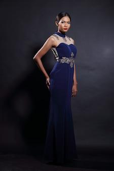 スリムなディープブルーのシルクレースのアジアンタンスキンウーマンモデルロングイブニングドレスのボールドレス、ファッションメイクブラックヘア、スタジオ照明暗い背景、全身スナップ