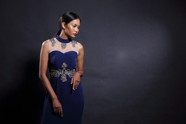 スリムなディープブルーのシルクレースのアジアの日焼け肌の女性モデル長いイブニングドレスのボールドレス、ファッションは黒い髪を構成し、スタジオ照明暗い背景、肖像画の半分のボディのコピースペース