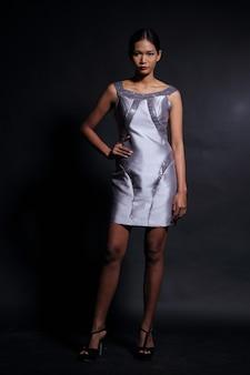 スリムなシルバーシルクの短いイブニングドレスのボールドレスのアジアの日焼け肌の女性モデル、ファッションは黒い髪を構成し、スタジオ照明暗い背景、全身スナップ