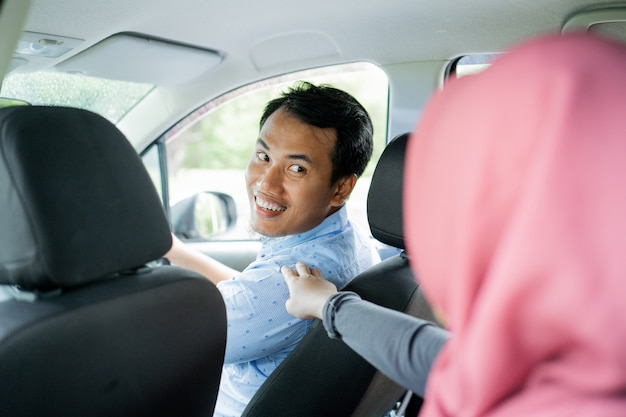 Asian taxi driver looking back after touch by hijab passenger