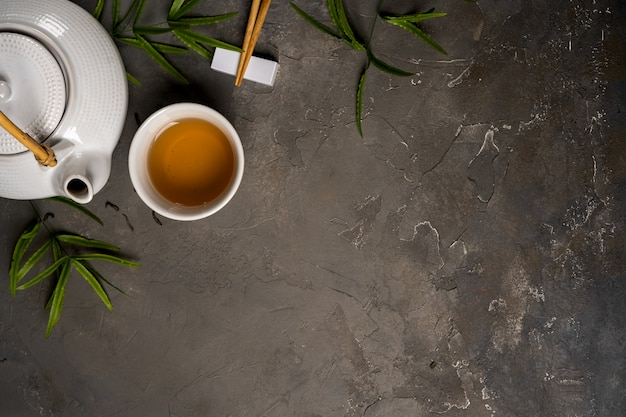 Asian tea concept, cup of tea and teapot surrounded with green tea dry leaves view from above