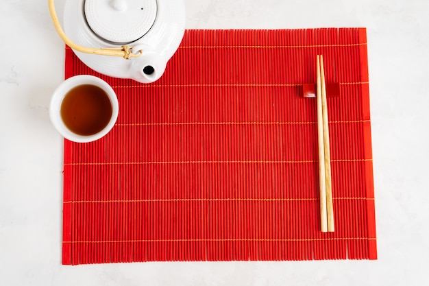 Asian tea food background. teapot and cup with chopsticks on the red bamboo mat over the gray stone background. mockup for the menu.