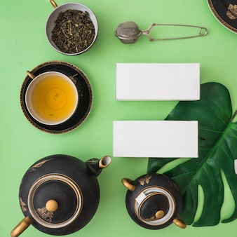 Asian tea set with herbal boxes on green backdrop