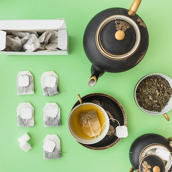Asian tea set with herbal tea bags on green backdrop
