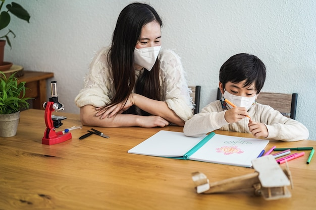 Asian teacher and child wearing protective face masks in classroom during coronavirus outbreak - focus on boy face