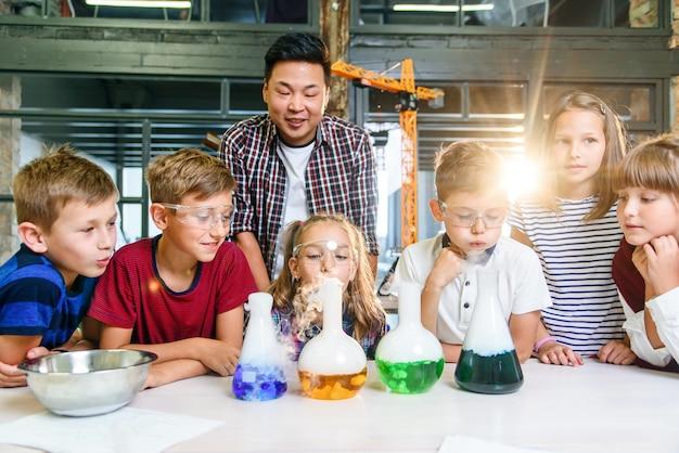 現代の学校の教室で子供たちのためにドライアイスの実験をしているアジアの教師。実験中、科学者は反応煙と着色液体を示すフラスコを保持しています。