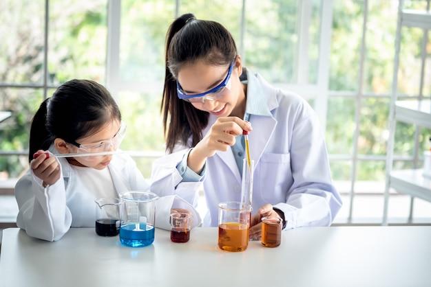 아시아 교사는 과학 실험실 교실의 흰색 테이블에서 과학 실험에 대해 소녀를 가르치고 있습니다.