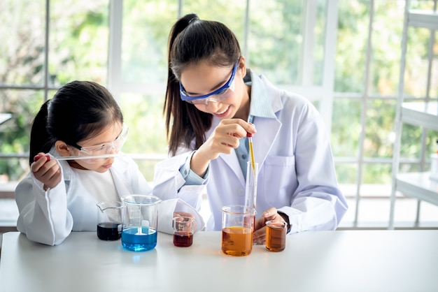 Asian teacher is teaching a girl, about scientific experiments on white table in a science lab classroom