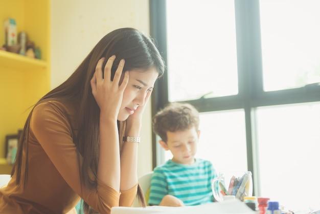 アジアの教師の幼稚園の手は、就学前の子供たちの議論で授業中の少年たちの、いたずらをやめさせずに彼女の両耳を閉じた。ヴィンテージエフェクトスタイルの写真。