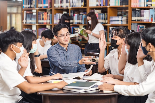 Asian teacher raising hand and giving lesson to group of college students