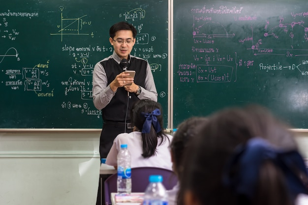 Asian teacher using the smart mobile phone for giving lesson over the the physics formula