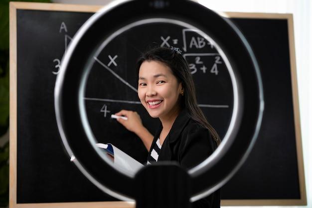 Vidio 카메라를 사용하여 가정에서 아시아 교사가 일하고 웹에서 학생을 가르치면이 이미지는 covid19, 교육, 교사 및 전자 학습 개념에 사용할 수 있습니다