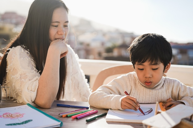 Asian teacher working with child boy at preschool outdoors in summer sunny day