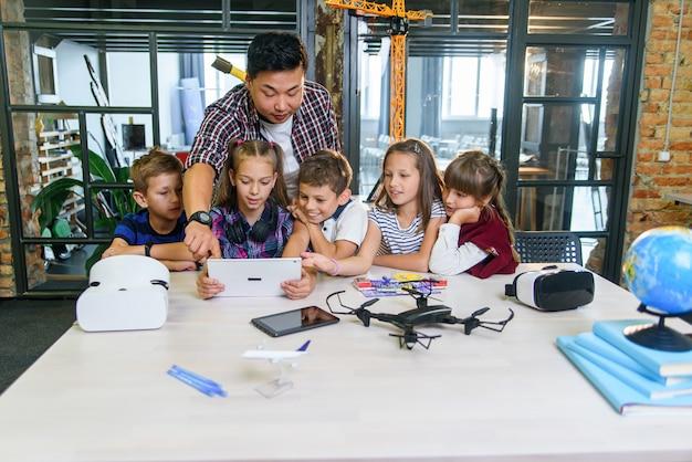 아시아 교사는 기술 수업에서 디지털 장치를 사용하는 다섯 명의 젊은 학생과 함께 일합니다. 교육, 과학, 개발 및 현대 기술 개념.