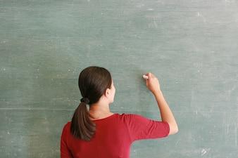 Asian teacher writing on blackboard with chalk in classroom