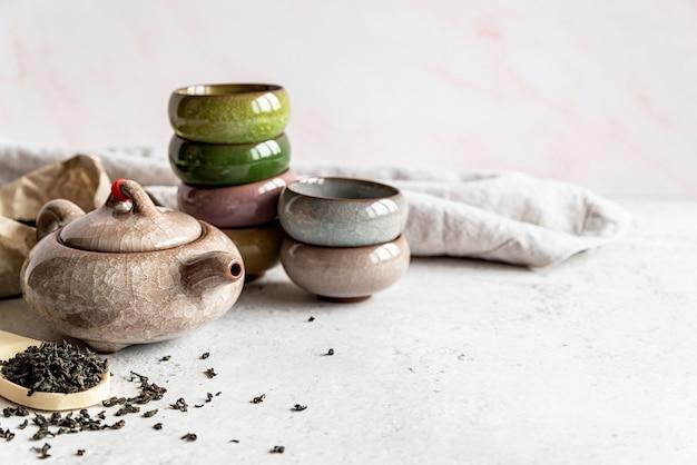 Азиатский чайник с кучей разноцветных чашек и пакет чая на фоне белого мрамора