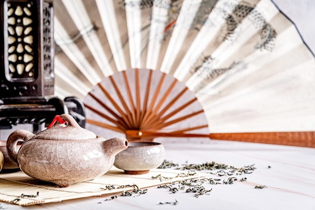 Asian teapot with teacups on bamboo table mat decorated with chinese fan