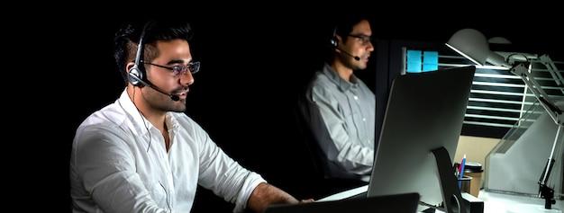 Азиатская техподдержка работает ночную смену в колл-центре