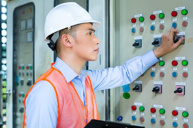 Asian technician at panel on construction site