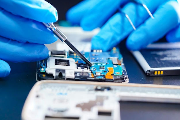 Asian technician repairing micro circuit main board of smartphone.