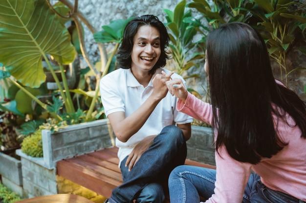 アジアの十代のカップルは庭でおしゃべりしながら有望な指の動きで座っています