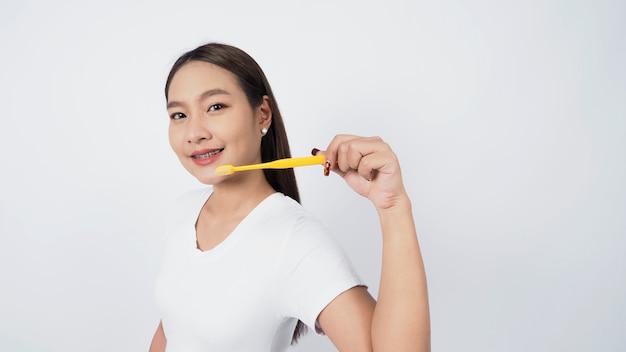 Азиатский подросток на лице с подтяжками и зубной щеткой, улыбаясь в камеру, чтобы показать стоматологические ортодонтические зубы, которые включают в себя профессиональный металлический проволочный материал от ортодонта