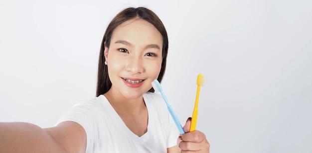 교정기와 치아 교정 치아를 보여주기 위해 카메라에 웃는 아시아 십대 얼굴 중괄호와 칫솔