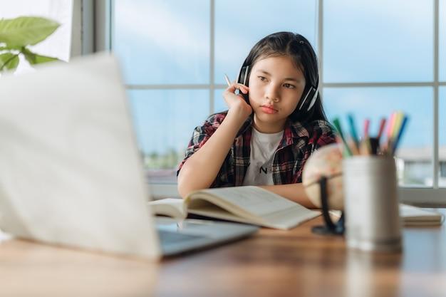 Азиатская девочка-подросток в наушниках изучает язык онлайн, использует ноутбук, смотрит на экран, выполняет школьные задания дома, пишет заметки, слушает лекцию или музыку, дистанционное образование