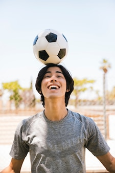 Asian teen student holding soccer ball on head