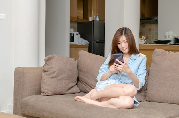 Asian teen using smartphone sitting on sofa