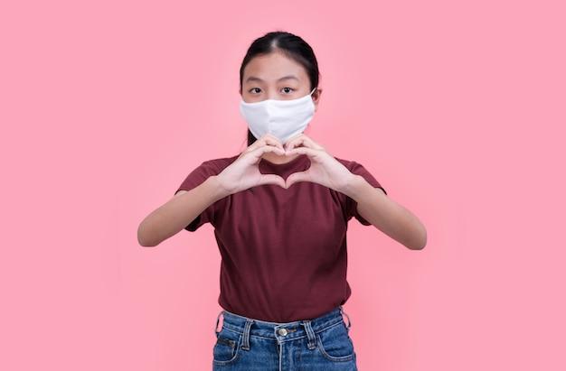 ピンクの医療マスクを身に着けているアジアの10代