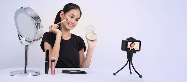 Asian teen woman sit in front of camera and live broadcasting as a beauty blogger influencer or youtuber to review or advice about how to make up at home.