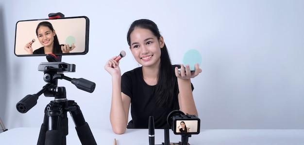 아시아 십대 여성이 카메라 앞에 앉아 뷰티 블로거 인플 루 언서 또는 유 튜버로 라이브 방송을 통해 집에서 화장하는 방법을 검토하거나 조언합니다.