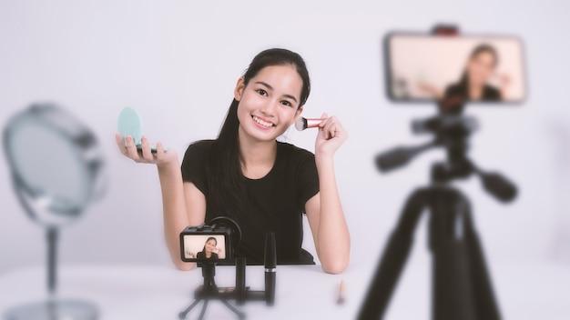 아시아 10대 여성이 카메라 앞에 앉아 뷰티 블로거 인플루언서로 생방송