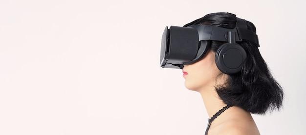 Vrまたはバーチャルリアリティヘッドセットを身に着けているアジアの10代の女性は、学習、旅行、ゲームなどのデジタルシミュレーションの世界に参入します。