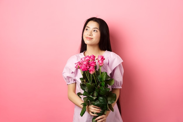 Asian teenage girl in cute dress looking romantic at empty space logo, holding valentines day flowers gift, receive boquet of roses from lover, standing on pink background.