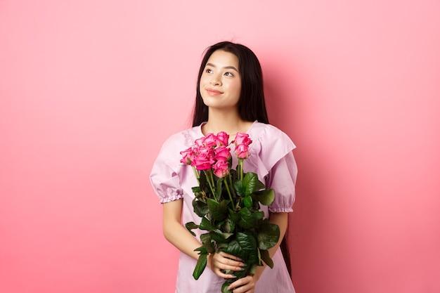 空のスペースのロゴをロマンチックに見て、バレンタインデーの花のギフトを保持し、ピンクの背景に立って、恋人からバラのボケを受け取るかわいいドレスを着たアジアの10代の少女。