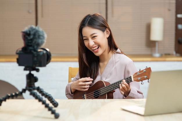 아시아 10대 소녀가 카메라를 보고 자신을 촬영하고 우쿨렐레 기타를 연주한다