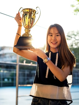 Asian teenage girl in sporty clothes holding up a trophy outdoors