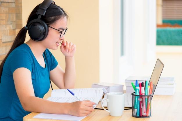 헤드셋과 안경을 쓴 아시아 10대 여학생은 학교에서 온라인으로 배우는 노트북 컴퓨터를 보고 마이크에 대고 말합니다. 집에서 대학 화상 통화 원격 교육 수업